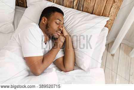 African American Man Sleeping Peacefully Resting With Eyes Closed Lying In Comfortable Bed In Bedroo