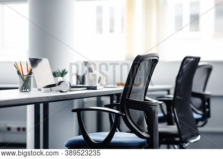 Modern Gadgets In Interior Of Coworking Office During Covid-19 Epidemic. Chairs And Desk For Support