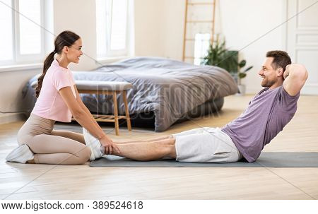 Sporty Couple Exercising Together Training Doing Abs Sit-ups At Home, Girlfriend Holding Boyfriends