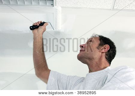 Painter using roller on ceiling