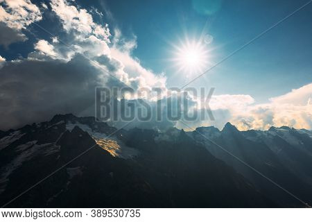 The Sun Is Shining Brightly Over The Cloudy Frozen Mountain Peaks. The Sun's Rays Shine On The Cauca