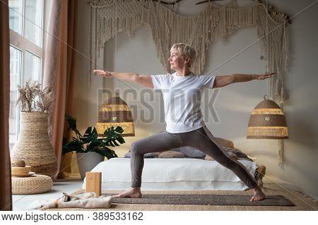 Senior Woman Practicing Yoga, Standing In Warrior Two Exercise, Virabhadrasana Ii Pose