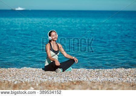 Cute Lady Enjoying Sun Sitting On Beach. Girl Listen To Music In Headset. Contemplation And Meditati