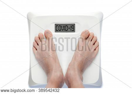 Feet On Digital Bathroom Scale With The Word Covid-19 On Screen. Concept Of Overweight Or Obese Peop