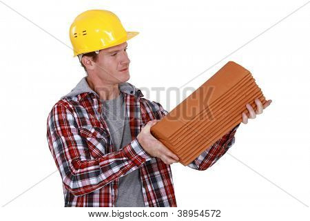 Roofer holding pile of tiles