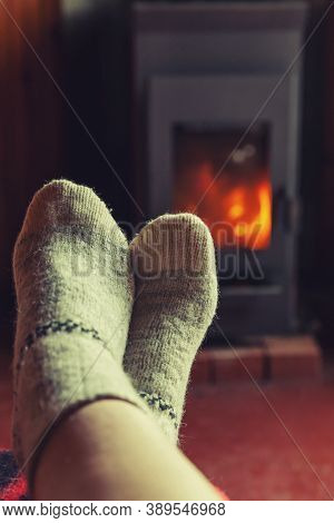 Feet Legs In Winter Clothes Wool Socks At Fireplace Background. Woman Sitting At Home On Winter Or A