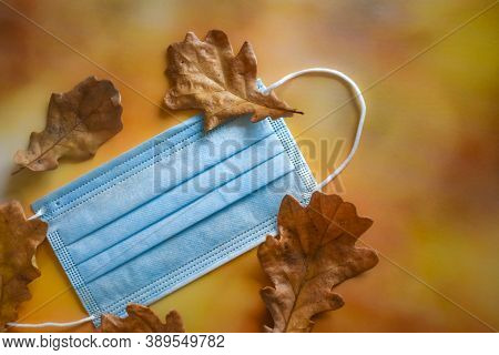 A Medical Protective Mask And Yellow Dry Oak Leaves Lie On A Bright Autumn Background. The Concept O
