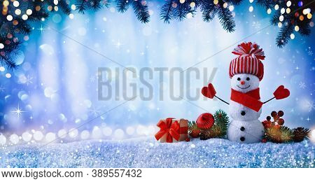 Christmas Or Winter Background With With Funny Snowman, Gift Box And Fir Tree Branches In Wintery Sc