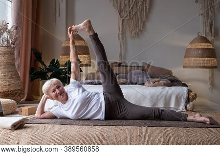 Woman Doing Fitness Workout, Exercise Stretching Legs, Anantasana Or Side Reclining Leg Lift Yoga Po