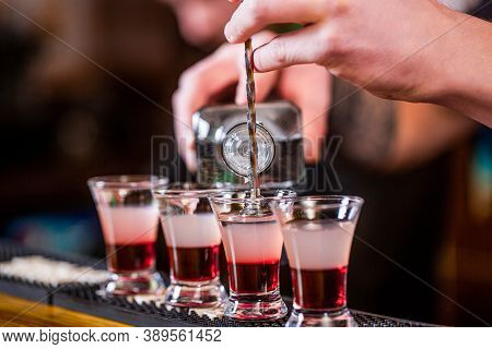 Bartender Pouring Strong Alcoholic Drink Into Small Glasses On Bar. Shots At The Nightclub. Red Alco