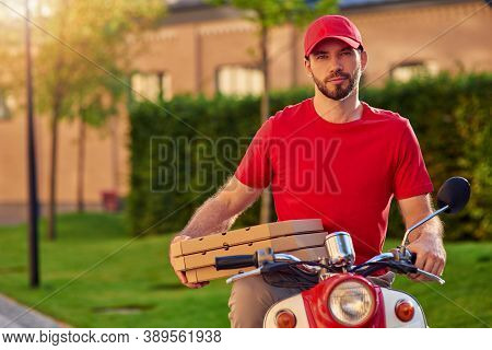 Young Handsome Caucasian Delivery Man Holding Pizza Boxes