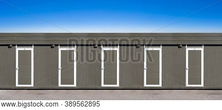Shipping Containers With Doors Converted Into Public Restrooms Or Construction Site Offices, Blue Sk