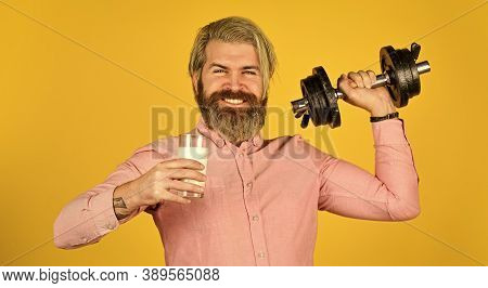 Amount Of Fat. Vitamins For Muscles. Sportsman Hold Dumbbell And Glass Of Milk. Protein Diet. Protei