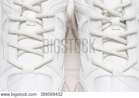 Part Of A White Sneakers With Laces. A Fragment Of White Shoes. A Piece Of Sneaker. Fashionable Snea