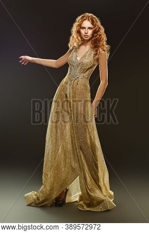 Full length monochrome portrait of a beautiful woman posing in motion in a luxury evening dress on dark background. Beauty, evening fashion.