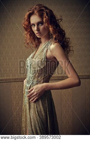 Portrait of a charming young woman with beautiful red hair posing in a luxury golden dress on vintage gold wallpaper background. Beauty, evening fashion.