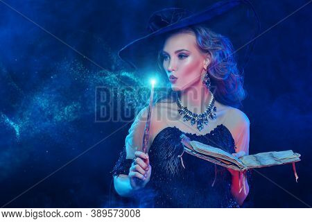 Portrait of a enchanting young witch in a hat and with a magic wand and book conjuring surrounded by magic lights on a dark background. Halloween celebration, party.