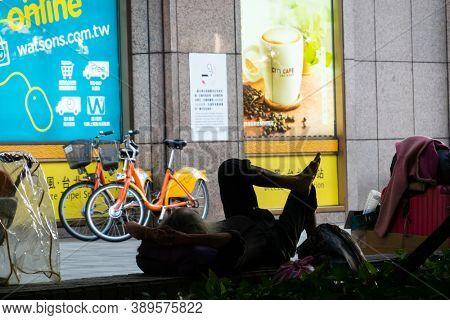 Taipei, Taiwan - Oct 1st, 2020:  homeless man sit and sleep at the outside of Taipei station, Taipei, Taiwan