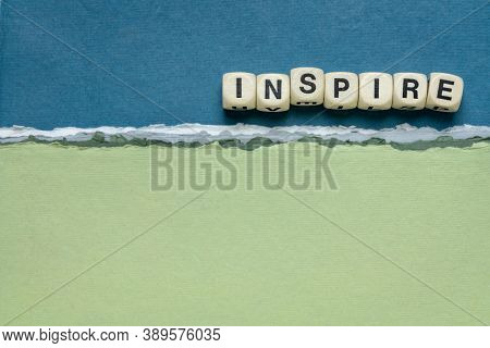 inspire word abstract in wooden letter cubes against handmade paper abstract in blue and green tones, inspiration, leadership and role model concept