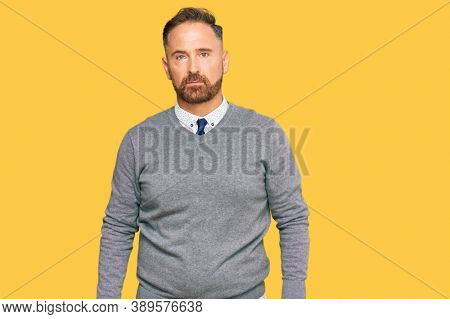 Handsome middle age man wearing business clothes relaxed with serious expression on face. simple and natural looking at the camera.