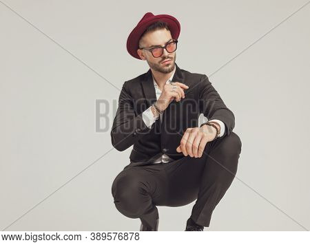 Motivated fashion model looking away, wearing sunglasses and hat while crouching on gray studio background