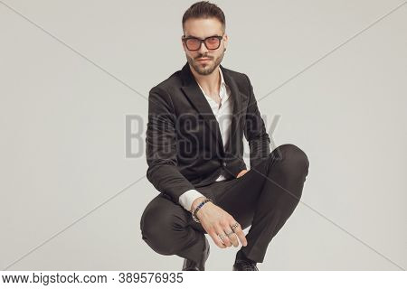 Confident fashion model looking forward and wearing sunglasses while crouching on gray studio background