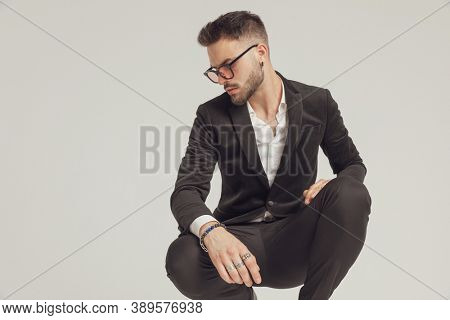 Thoughtful fashion model looking down and wearing sunglasses while crouching on gray studio background