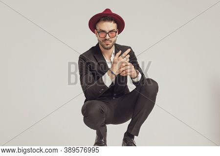 Positive fashion model adjusting his rings and smiling, wearing sunglasses and hat while crouching on gray studio background