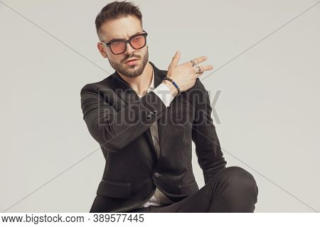 Arrogant fashion model cleaning his shoulder, wearing sunglasses while crouching on gray studio background