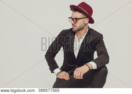 Confident fashion model curiously looking away, wearing sunglasses and hat while crouching on gray studio background