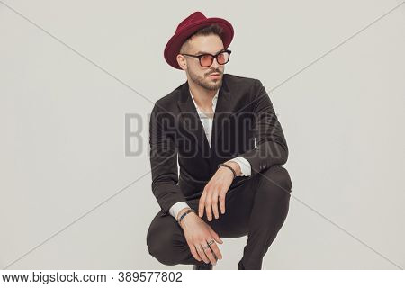 Eager fashion model looking away, wearing hat and sunglasses while crouching on gray studio background