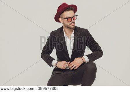 Confident fashion model adjusting his jacket, wearing sunglasses and hat while crouching on gray studio background