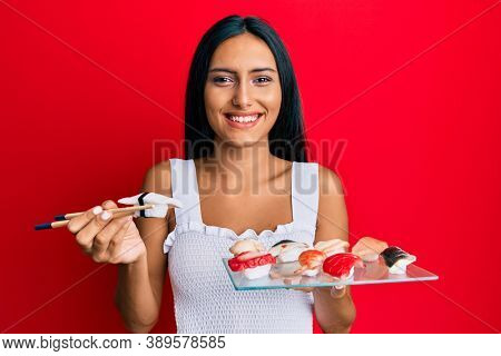 Young brunette woman eating butterfish sushi using chopsticks smiling with a happy and cool smile on face. showing teeth.