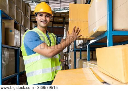 Indian warehouse worker put cardboard box in to shelf with muslim Islam asian worker do inventory in warehouse distribution center environment. Using in business warehouse and logistic concept.