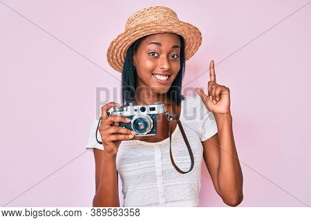 Young african american woman wearing summer hat holding vintage camera with a big smile on face, pointing with hand finger to the side looking at the camera.