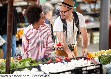 Sales of fresh and organic vegetables and  fruits at the green market or farmers market.  Young couple choose and buy products for healthy food in grocery. All for diet healthy eating, lifestyle.