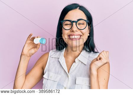 Beautiful young woman holding glasses and contact lenses screaming proud, celebrating victory and success very excited with raised arm
