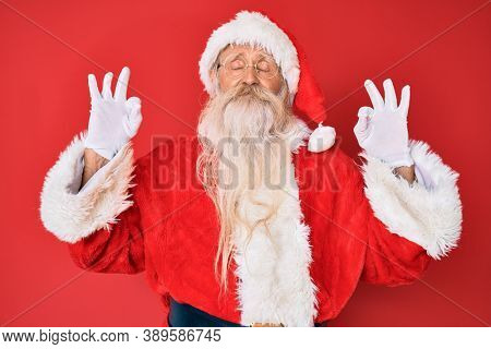 Old senior man with grey hair and long beard wearing traditional santa claus costume relax and smiling with eyes closed doing meditation gesture with fingers. yoga concept.