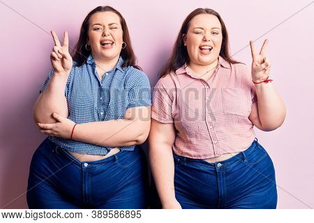 Young plus size twins wearing casual clothes smiling with happy face winking at the camera doing victory sign with fingers. number two.