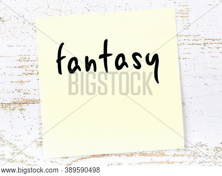 Concept Of Reminder About Fantasy. Yellow Sticky Sheet Of Paper On Wooden Wall With Inscription