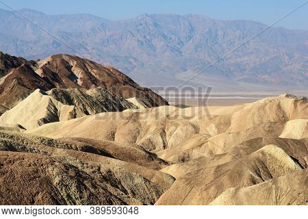 Arid Hills Surrounding Canyons With A Rural Plateau And Barren Mountains Beyond Taken At Zabriskie P