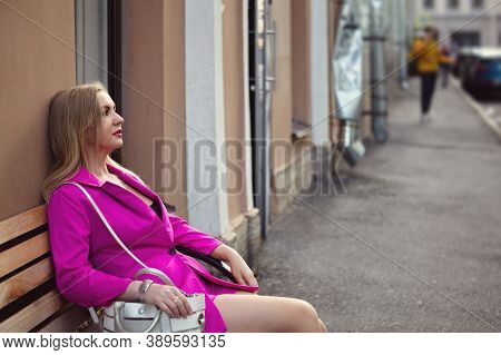 A Woman In Pink Sits On A Bench In The Center Of A European City.