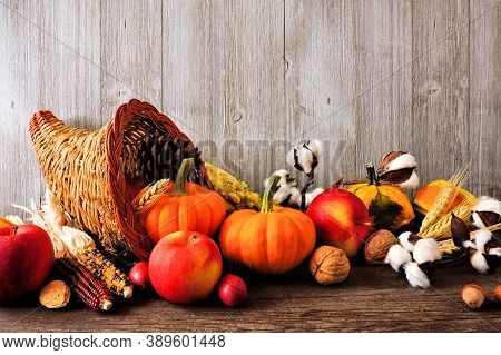Thanksgiving Harvest Cornucopia Filled With Autumn Fruits And Vegetables. Side View Against A Rustic