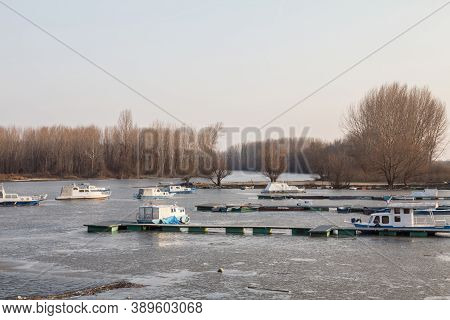 Panorama Of The Port Of Kovin, On The Danube, With Boats And Ship Anchored In Frozen Waters In Winte
