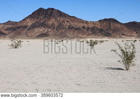 Sand On An Arid Plateau With Barren Mountains Beyond Taken In The Rural Mojave Desert, Ca