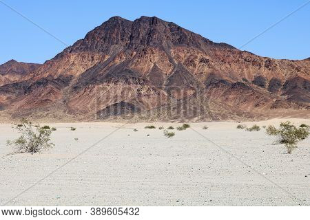 Arid Sandy Plateau Surrounding A Barren Mountain With Colorful Rocks Representing Mineral Deposits T