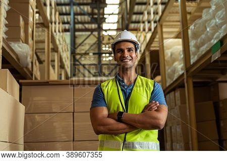 Portrait Of Young Indian Industrial Worker With Arm Folded Working In Logistic Industry Indoor Insid