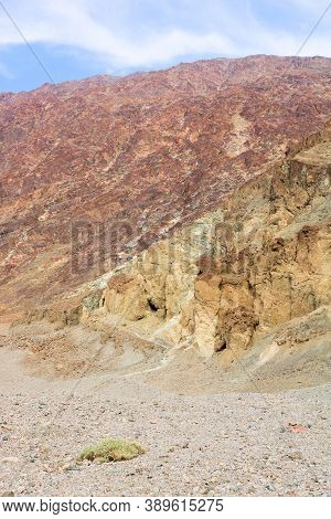 Arid Plateau Covered With Sand Besides A Barren Mountain Ridge Taken In Death Valley, Ca