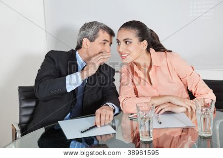 Manager whispering a secret into the ear of a businesswoman