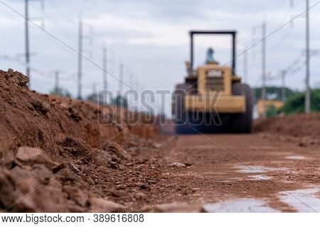 Blurred Yellow Vibratory Soil Compactor Working On Road Construction, Yellow Vibratory Soil Compacto